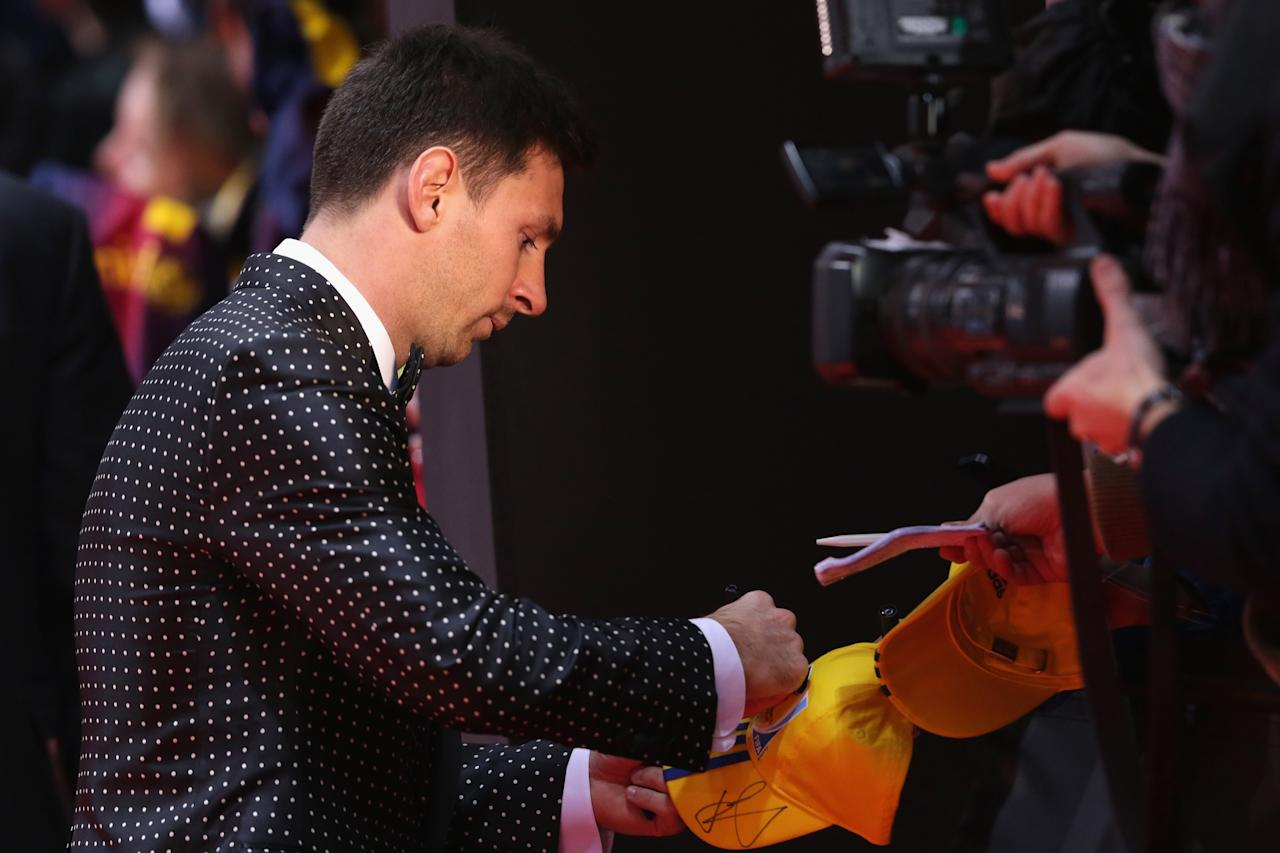 ZURICH, SWITZERLAND - JANUARY 07:  Lionel Messi signs autographs poses during the red carpet arrivals for the FIFA Ballon d'Or Gala 2012 on January 7, 2013 at Congress House in Zurich, Switzerland.  (Photo by Christof Koepsel/Getty Images)