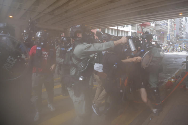 Riot Police use pepper spray to protesters during a protest against Beijing's national security legislation in Causeway Bay in Hong Kong, Sunday, May 24, 2020. Hong Kong police fired volleys of tear gas in a popular shopping district as hundreds took to the streets Sunday to march against China's proposed tough national security legislation for the city. (AP Photo/Kin Cheung)