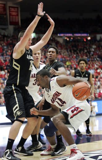 Arizona's Soloman Hill (44) tries to drive against Colorado's Shane Harris-Tunks (15) and Xavier Johnson, rear, during the first half of an NCAA college basketball game at McKale Center in Tucson, Ariz., Thursday, Jan 3, 2013. (AP Photo/John Miller)