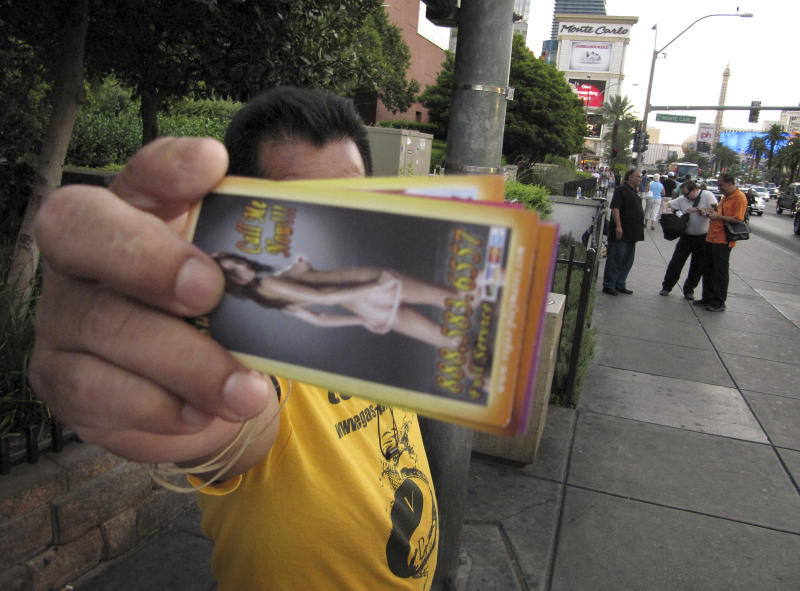 "An unidentified man on a Las Vegas Strip sidewalk hands out cards advertising exotic dancers on Wednesday, Aug. 29, 2012. Las Vegas officials have passed a litter ordinance requiring such ""handbillers"" to pick up after tourists who drop the materials. The American Civil Liberties Union says the new ordinance might violate free speech protections. (AP Photo/Mead Gruver)"