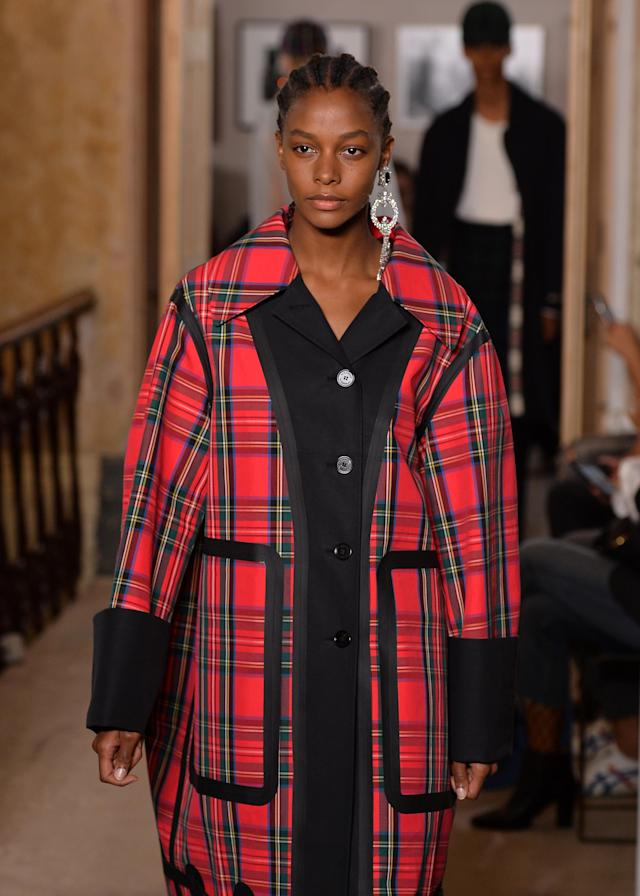 Model wears a crystal chandelier monocle earring and tartan coat from the Burberry September 2017 collection. (Photo: Getty Images)