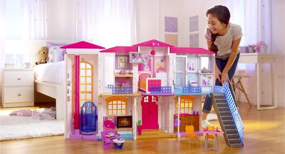 Young girl with a Barbie Dream House