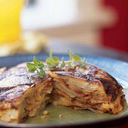 """<p>Tortilla Española (its relation to Mexican tortillas comes solely from it round shape) is among the most popular dishes in Spain. Although its ingredients couldn't be more basic--potatoes, eggs, onions, and oil--they're combined and cooked in a way that makes this dish irresistible and versatile. <a href=""""https://www.myrecipes.com/t/vegetables/potatoes"""" rel=""""nofollow noopener"""" target=""""_blank"""" data-ylk=""""slk:The potatoes"""" class=""""link rapid-noclick-resp"""">The potatoes</a> are normally fried, but we've roasted them with excellent results. Unlike American omelets, this one's best made several hours ahead then served at room temperature.</p>"""