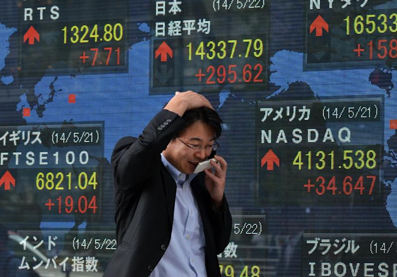 A man passes before a share prices board in Tokyo on May 22, 2014