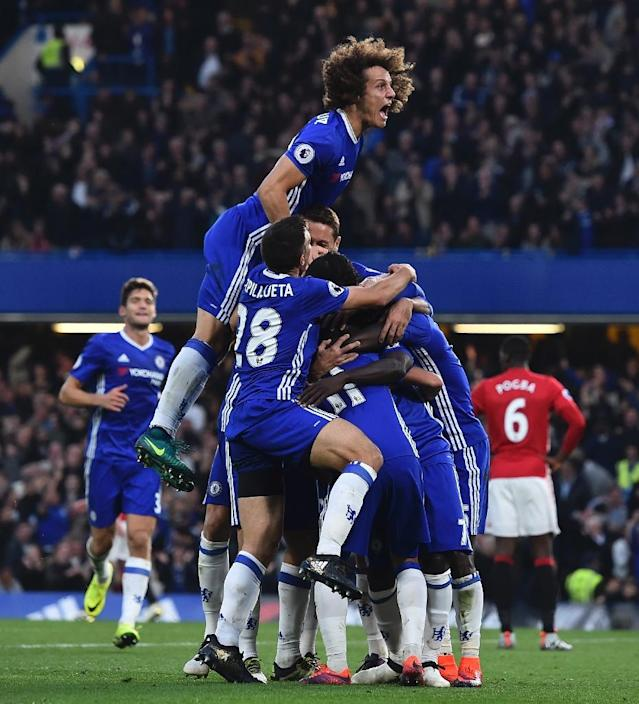 Chelsea's defender David Luiz (top) jumps onto the huddle to join the celebration after N'Golo Kante scored their fourth goal in London on October 23, 2016 (AFP Photo/Glyn Kirk)