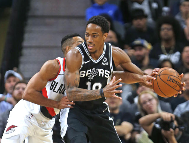 C.J. McCollum of the Portland Trail Blazers tries to knock the ball away from DeMar DeRozan on Sunday in San Antonio. (Getty Images)