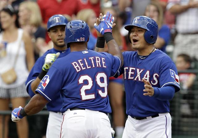 Texas Rangers third baseman Adrian Beltre is congratulated by Shin-Soo Choo, right, of South Korea and Alex Rios, rear, after Beltre hit a two-run home run off of Minnesota Twins' Kevin Correia that scored Choo in the first inning of a baseball game, Friday, June 27, 2014, in Arlington, Texas. (AP Photo/Tony Gutierrez)