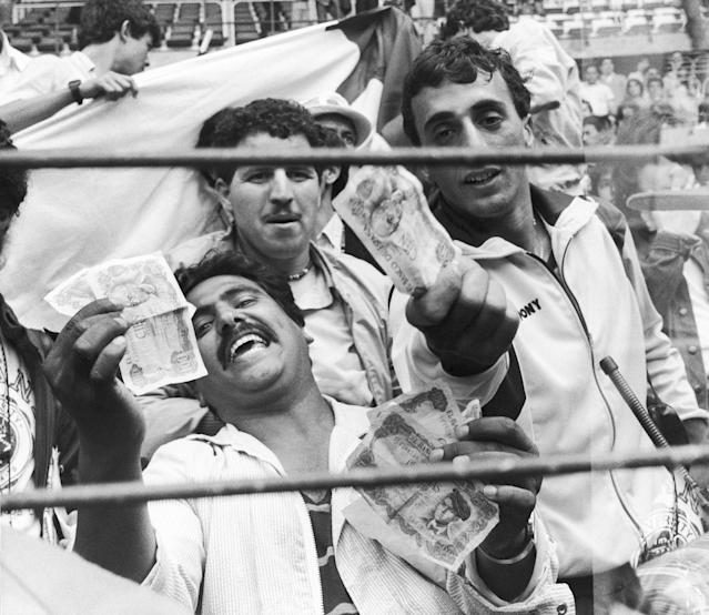 FILE - In this June 25, 1982 file photo, Algerian soccer fans show money to photographers, in Gijon, Spain, after the World Cup soccer match between West Germany and Austria, one of the most controversial in World Cup history. West Germany beat Austria 1-0, a result that meant both teams progressed to the next round at Algeria's expense. The 21st World Cup begins on Thursday, June 14, 2018, when host Russia takes on Saudi Arabia. (AP Photo/File)