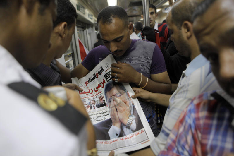 Egyptians read a newspaper fronted by a picture of Egypt's newly elected President Mohammed Morsi in Cairo, Egypt, Monday, June 25, 2012. The new Egyptian president Mohammed Morsi moved first thing Monday morning into the office once occupied by his ousted predecessor Hosni Mubarak and started work on forming a government even before he had a clear picture of what he could do after the ruling military stripped most of the major powers from his post. (AP Photo/Amr Nabil)