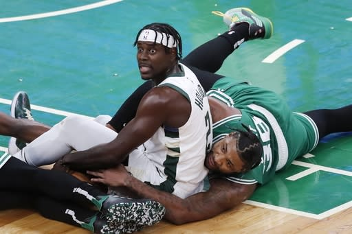 Milwaukee Bucks' Jrue Holiday (21) looks for a call after he and Boston Celtics' Marcus Smart (36) scrambled for a loose ball during the first half of an NBA basketball game Wednesday, Dec. 23, 2020, in Boston. (AP Photo/Michael Dwyer)