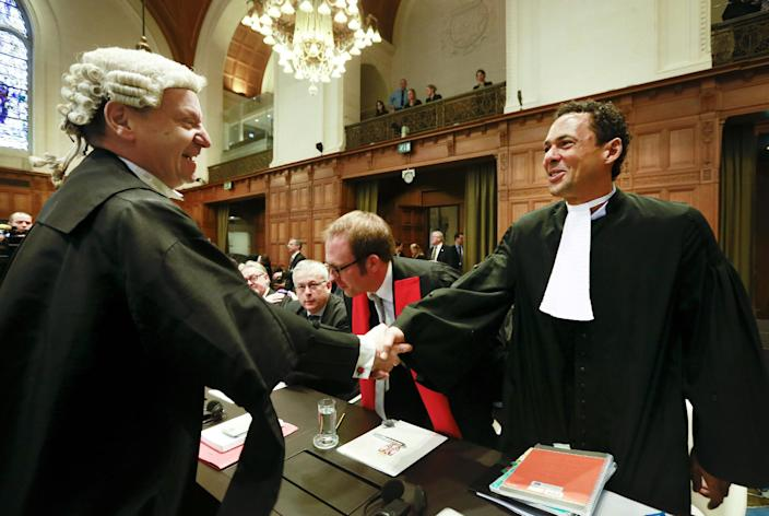 Counsel Philippe Sands of Croatia, left, shakes hands with Wayne Jordash of the Serbia delegation, right, prior to the start of public hearings at the International Court of Justice (ICJ) in The Hague, Netherlands, Monday, March 3, 2014. Croatia is accusing Serbia of genocide during fighting in the early 1990's as the former Yugoslavia shattered in spasms of ethnic violence, in a case at the United Nations' highest court that highlights lingering animosity in the region. Croatia is asking the ICJ to declare that Serbia breached the 1948 Genocide Convention when forces from the former Federal Republic of Yugoslavia attempted to drive Croats out of large swaths of the country after Zagreb declared independence in 1991. (AP Photo/Jiri Buller)