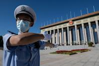 A police officer directs official cars outside the Great Hall of the People ahead of a ceremony to honor people who fought against the Covid-19 coronavirus pandemic in September 2020