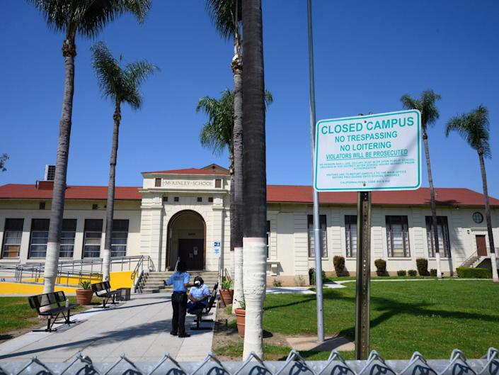 Two security guards talk on the campus of the closed McKinley School, part of the Los Angeles Unified School District (LAUSD) system, in Compton, California, just south of Los Angeles: (2020 Getty Images)