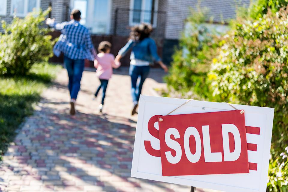 family running to new house with sold signboard on foreground