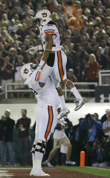 Auburn's Chad Slade lifts teammate Tre Mason after Mason 's touchdown run during the first half of the NCAA BCS National Championship college football game against Florida State Monday, Jan. 6, 2014, in Pasadena, Calif. (AP Photo/David J. Phillip)
