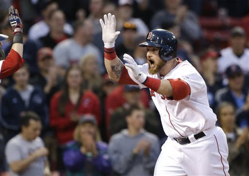 Boston Red Sox's Jonny Gomes celebrates his grand slam as he approaches home plate during the first inning of a baseball game against the Minnesota Twins at Fenway Park in Boston, Wednesday, May 8, 2013. (AP Photo/Elise Amendola)