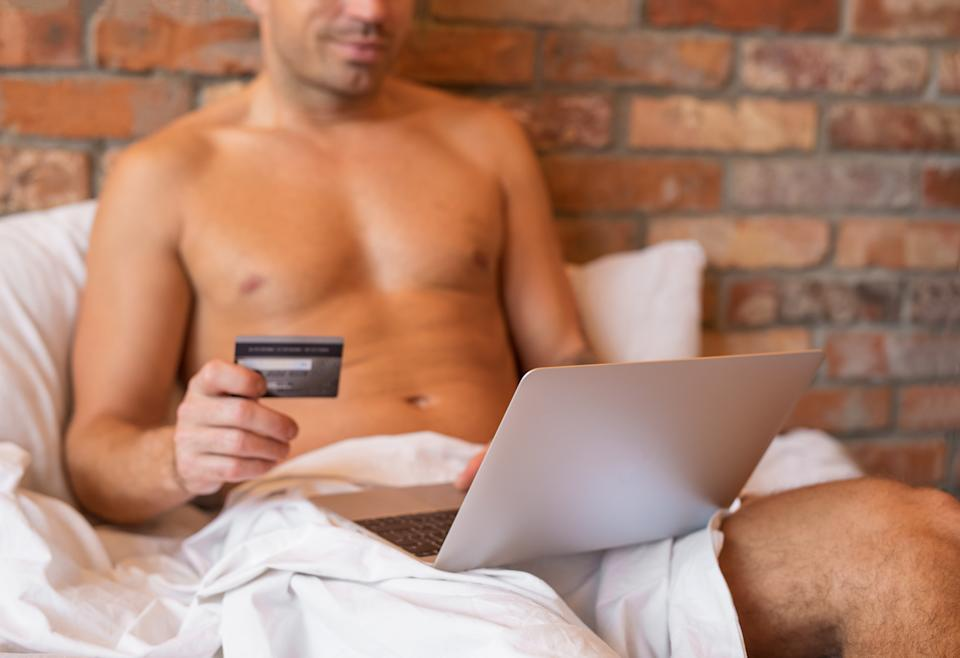 Man sitting in bed and paying with credit card for something using laptop