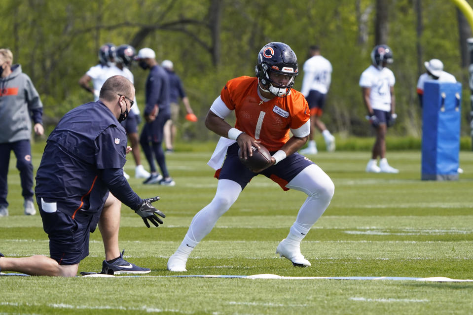 Chicago Bears quarterback Justin Fields (1) looks to hand off the ball during the NFL football team's rookie minicamp Friday, May, 14, 2021, in Lake Forest Ill. (AP Photo/David Banks, Pool)