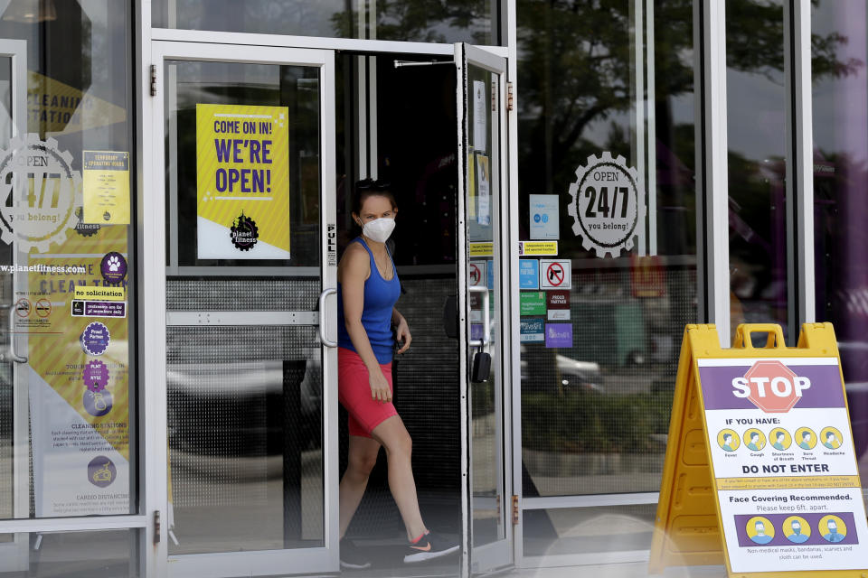 A person wears a mask while leaving a Planet Fitness gym location during the coronavirus pandemic, in Des Plaines, Ill., Wednesday, July 29, 2020. Planet Fitness will require masks at all locations beginning Aug. 1. Currently, all Planet Fitness employees are required to wear masks. (AP Photo/Nam Y. Huh)