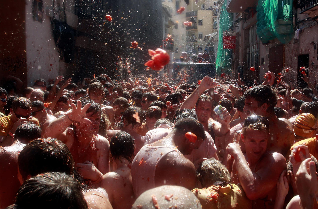"Revelers throw tomatoes during the annual ""tomatina"" tomato fight fiesta in the village of Bunol, near Valencia, Spain, Wednesday, Aug. 29, 2012. Bunol's town hall estimated more than 40,000 people, some from as far away as Japan and Australia, took up arms Wednesday with 100 tons of tomatoes in the yearly food fight known as the 'Tomatina' now in its 64th year. (AP Photo/Alberto Saiz)"