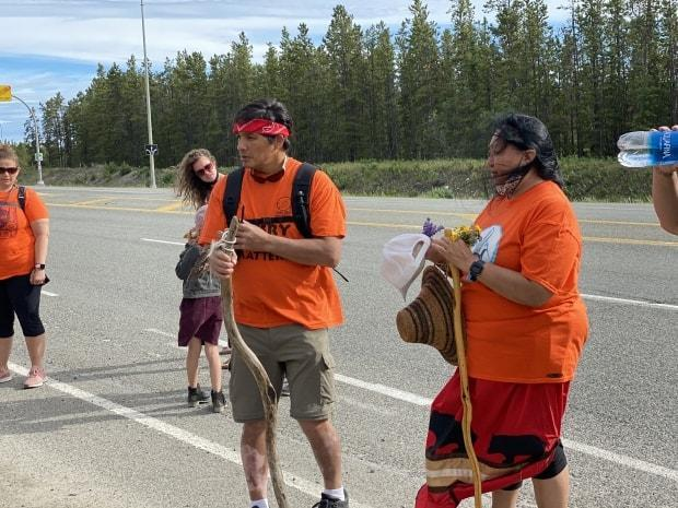 James Henyu, centre left, and Jacqueline Shorty, right, with a group of local supporters last month, right before leaving Whitehorse on their walk to Kamloops, B.C. (Chris MacIntyre/CBC - image credit)