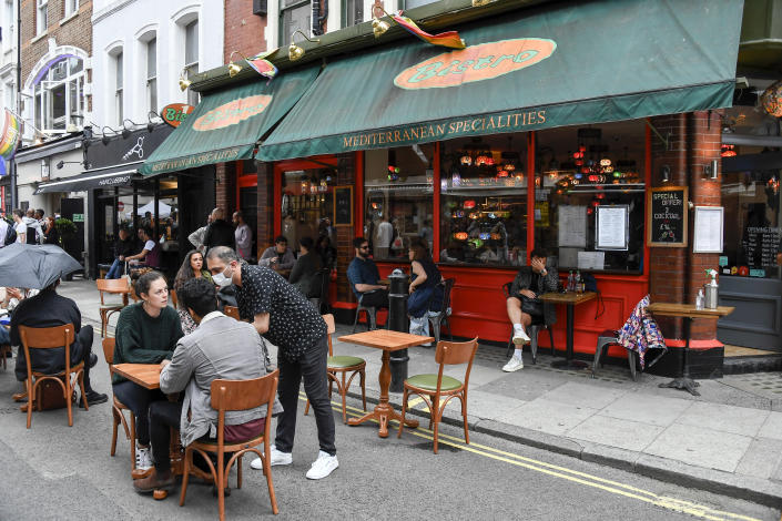 People sit and drink, outside a restaurant in Soho, as the capital is set to reopen after the lockdown due to the Coronavirus outbreak, in London, Saturday, July 4, 2020. England is embarking on perhaps its biggest lockdown easing yet as pubs and restaurants have the right to reopen for the first time in more than three months. In addition to the reopening of much of the hospitality sector, couples can tie the knot once again, while many of those who have had enough of their lockdown hair can finally get a trim. (AP Photo/Alberto Pezzali)