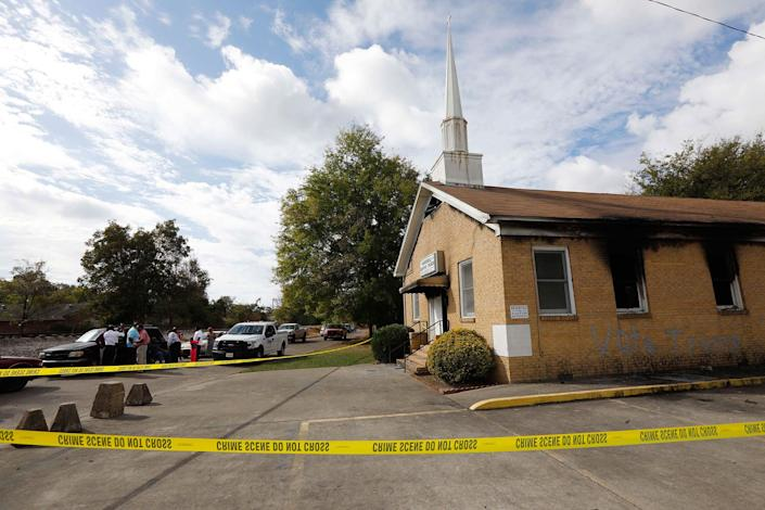 """<p>Area residents and church members observe as authorities investigate the fire damaged Hopewell M.B. Baptist Church in Greenville, Miss., Wednesday, Nov. 2, 2016. """"Vote Trump"""" was spray-painted on an outside wall of the black member church. Fire Chief Ruben Brown tells The Associated Press that firefighters found flames and smoke pouring from the sanctuary of the church just after 9 p.m. Tuesday. (AP Photo/Rogelio V. Solis) </p>"""