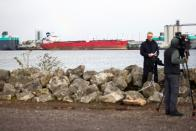 A news crew stand across the water from the Liberia-flagged oil tanker Nave Andromeda at Southampton Docks, following a security incident aboard the ship the night before off the coast of Isle of Wight, in Southampton