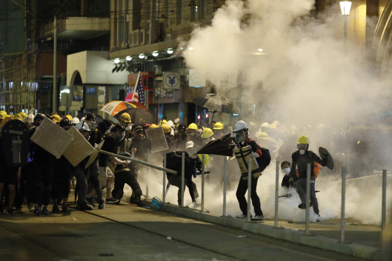 Protesters react to teargas as they confront riot police officers in Hong Kong on Sunday, July 21, 2019. Protesters in Hong Kong pressed on Sunday past the designated end point for a march in which tens of thousands repeated demands for direct elections in the Chinese territory and an independent investigation into police tactics used in previous demonstrations. (AP Photo/Vincent Yu)