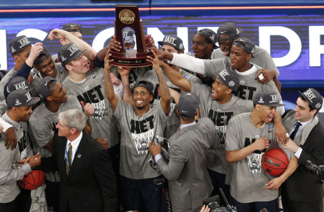 Connecticut players celebrate after defeating Michigan State during a regional final at the NCAA college basketball tournament, Sunday, March 30, 2014, in New York. (AP Photo/Julio Cortez)