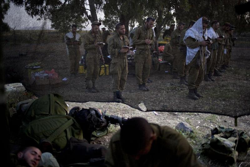 Israeli soldiers of the Golani brigade, few covered in a prayer shawls gather for the morning prayer before a military exercise in the Israeli controlled Golan Heights, near the border with Syria, Tuesday, May 7, 2013. (AP Photo/Ariel Schalit)