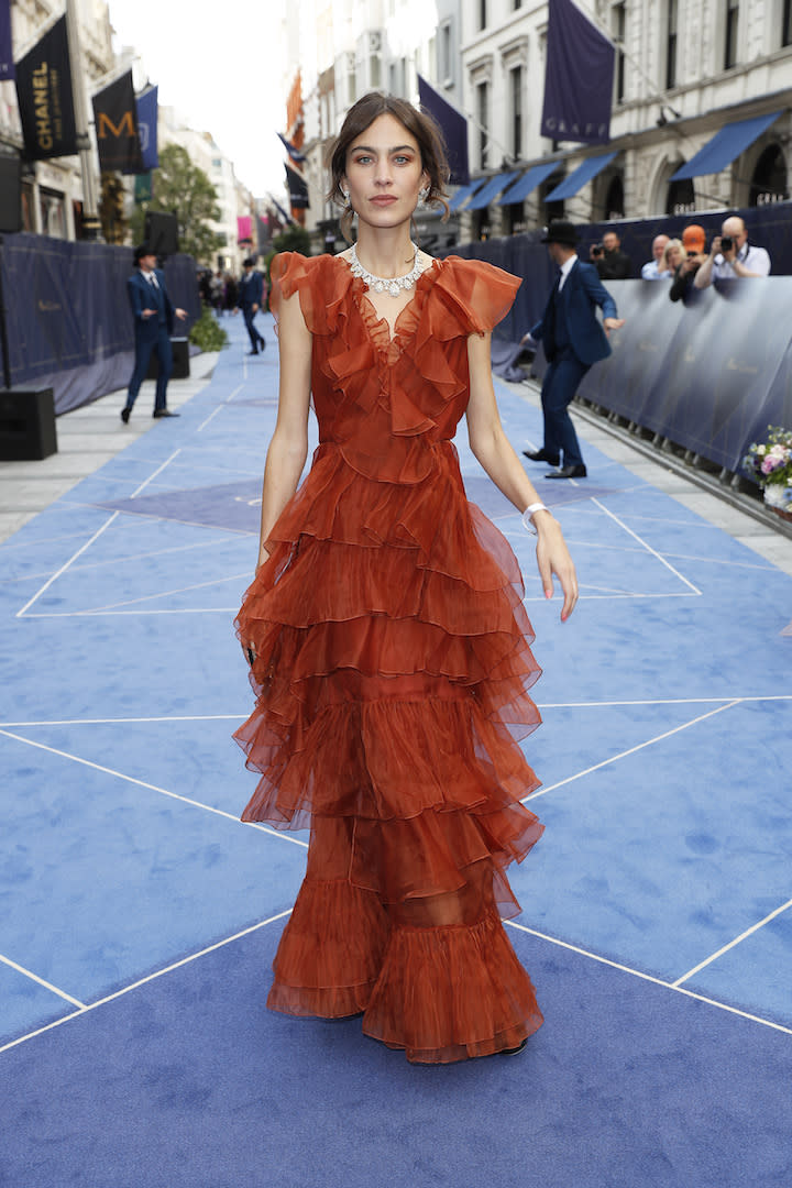 Another day, another look we need recreate. Alexa Chung chose a fiery orange ruffled frock by Johanna Ortiz for the star-studded party. <em>[Photo: Getty]</em>