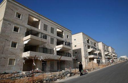 An ultra-Orthodox Jewish man walks past buildings under construction in the Israeli settlement of Beitar Ilit, in the occupied West Bank December 22, 2016. REUTERS/Baz Ratner