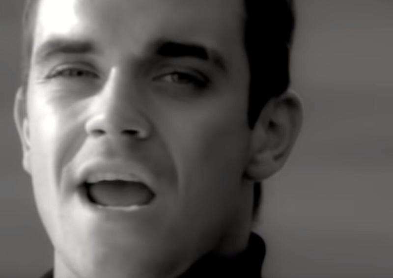 Robbie Williams sings in the music video for his 1997 single 'Angels'. (Credit: YouTube/Chrysalis Records)