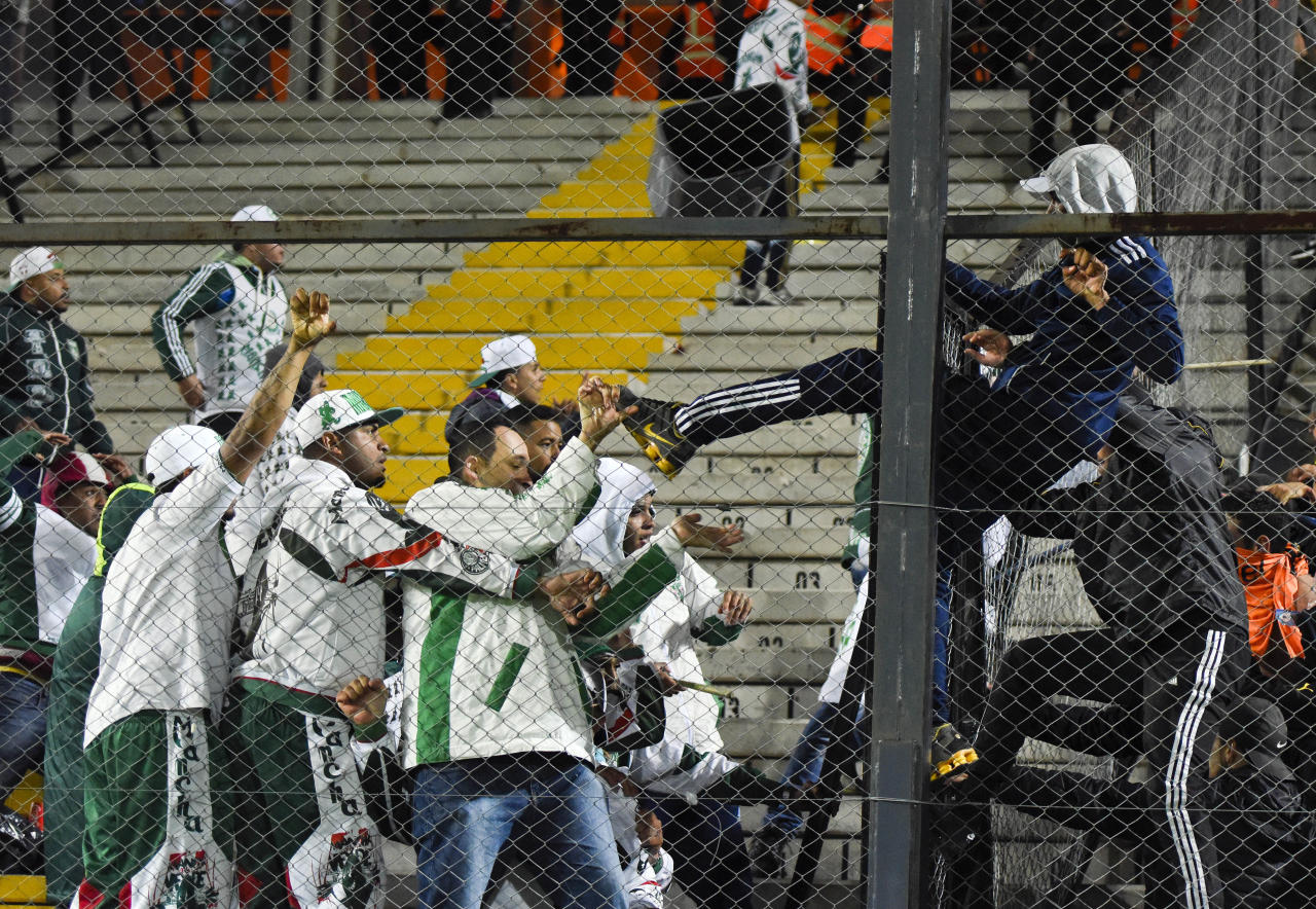 A fan of Uruguay's Penarol, right, fights with fans of Brazil's Palmeiras at the end of a Copa Libertadores soccer match in Montevideo, Uruguay, Thursday, April 27, 2017. Palmeiras won the match 3-2. (AP Photo/Matilde Campodonico)