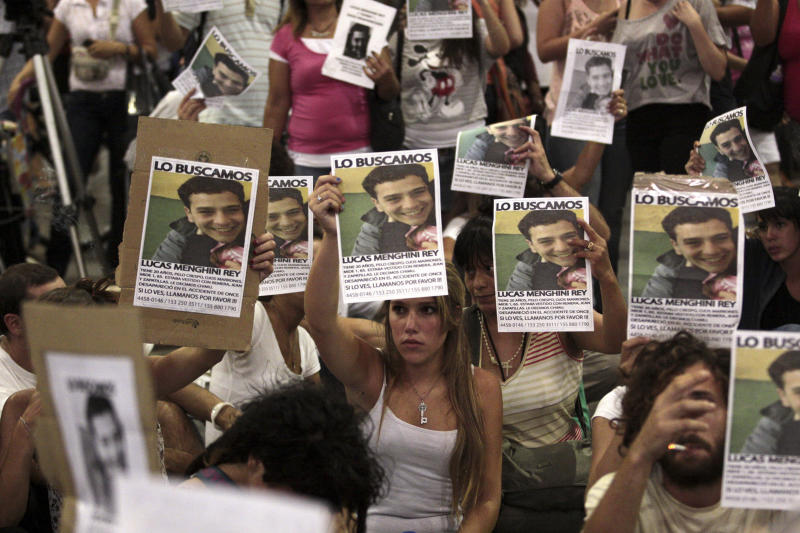 """Friends and relatives of Lucas Menghini Rey hold up posters with images of him that reads in Spanish """"We are looking for him"""" as they protest against authorities in Buenos Aires, Argentina, Friday Feb. 24, 2012. Argentine police have identified the 51st victim of Wednesday's train wreck as Lucas Menghini Rey, whose family's desperate search was emblematic of anger at the failure to protect people from long-known safety problems. (AP Photo/Alberto Raggio, DyN)"""