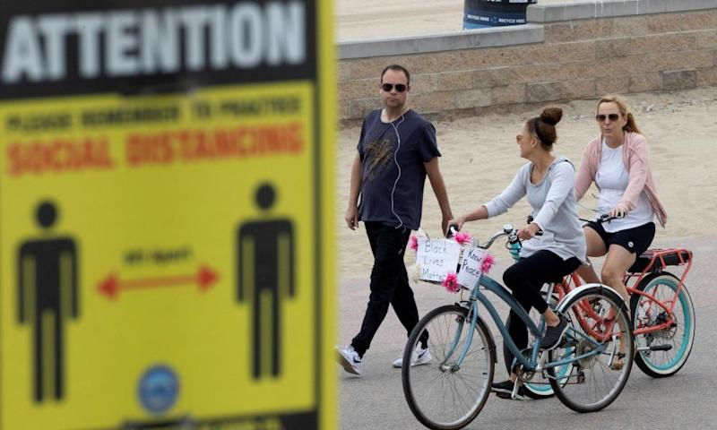 People choose not to wear face masks the boardwalk in Huntington Beach, California, on 1 July.