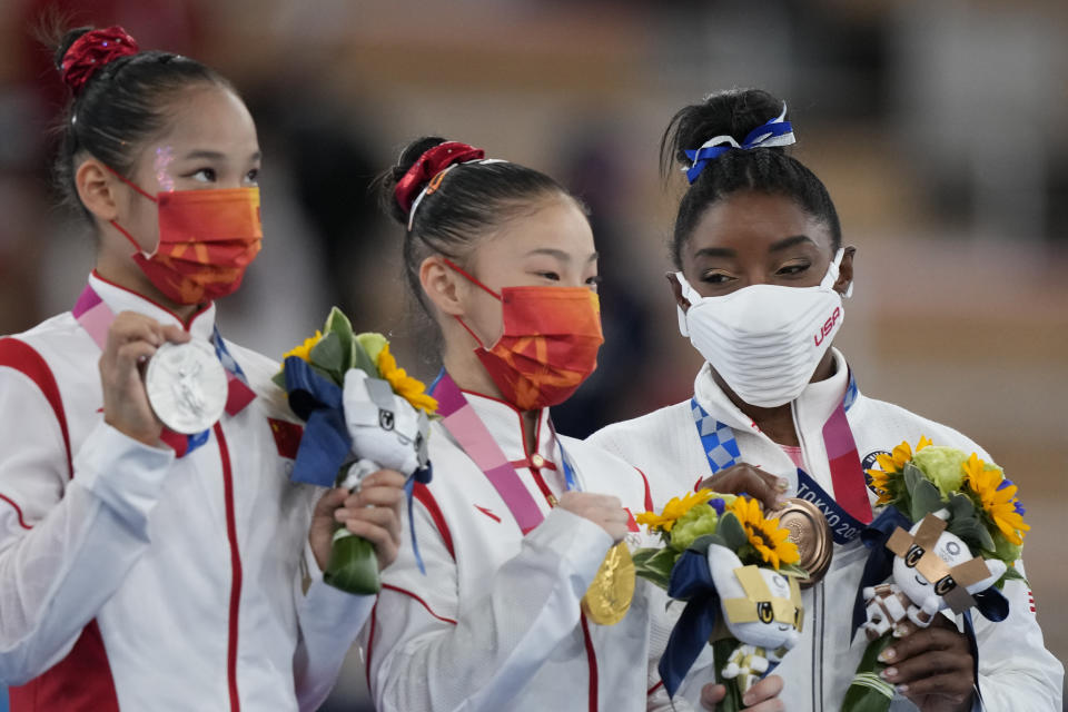 From left, silver medallist Tang Xijing, of China, gold medallist Guan Chenchen, of China, and bronze medallist Simone Biles, of the United States, pose with their medals for the balance beam during the artistic gymnastics women's apparatus final at the 2020 Summer Olympics, Tuesday, Aug. 3, 2021, in Tokyo, Japan. (AP Photo/Natacha Pisarenko)