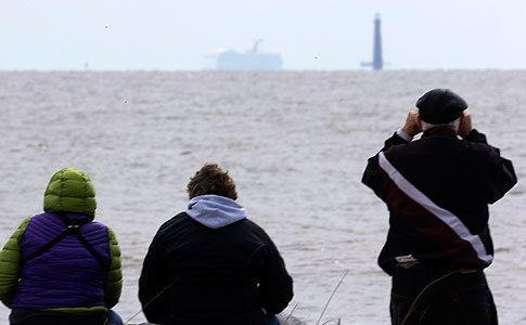 Residents sit on the shore and watch as the cruise ship Carnival Triumph is visible near Dauphin Island, Alabama. Photo: AP