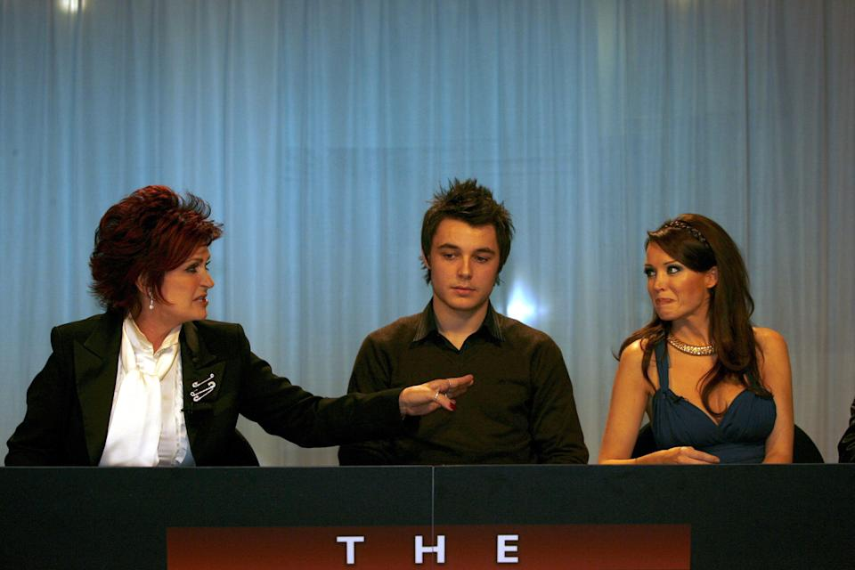 """When Dannii Minogue was added to the 'X Factor' judging panel in its fourth series, Sharon Osbourne was suitably unimpressed. <br /><br />She was able to mask it well enough at first, but by the end of the series, she was running around the 'Graham Norton Show' studio, doing an unflattering impression of the Australian judge, making fun of her Botox and eventually comparing Dannii's face to her own bum.<br /><br />Charming.<br /><br />Dannii never retaliated until years later, when she detailed Mrs O's treatment of her in her autobiography, with Kelly Osbourne wading in on Twitter and branding the 'Put The Needle On It' singer """"the devil"""".<br /><br />Literally. """"The devil"""". That's what someone said about Dannii Minogue."""