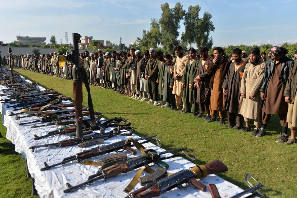 In this photograoh taken on November 17, 2019 members of the Islamic State (IS) group stand alongside their weapons, following they surrender to Afghanistan's government in Jalalabad, capital of Nangarhar Province. (Noorullah Shirzada/AFP via Getty Images)