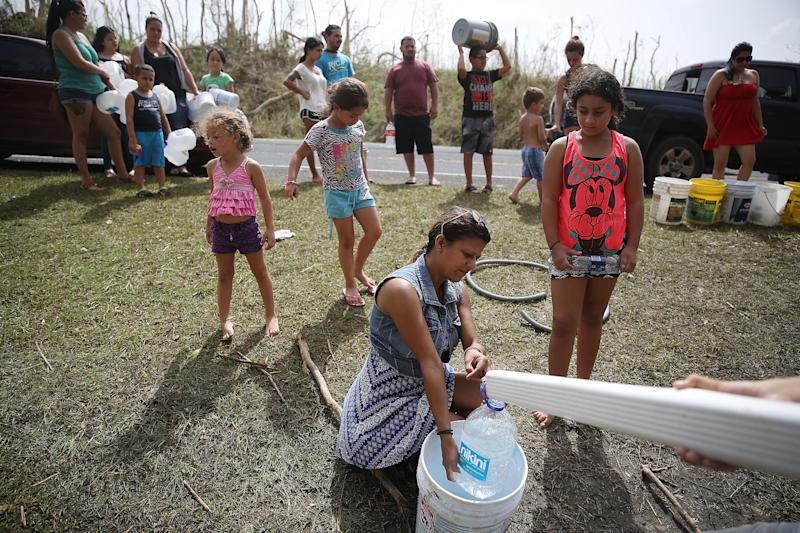 People in Corazal, Puerto Rico, fill containers with water from a natural spring on the side of the road as people deal with the aftermath of Hurricane Maria. (Joe Raedle via Getty Images)