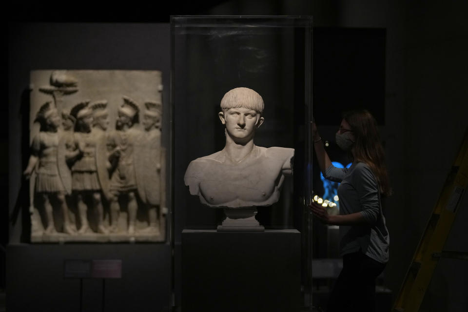 """A museum employee poses for photographers next to a marble bust of Roman emperor Nero dating from about AD 54-59 from Olbia, on the island of Sardinia in Italy, during a media preview for the """"Nero: the man behind the myth"""" exhibition, at the British Museum in London, Monday, May 24, 2021. The exhibition, which opens to visitors on May 27 and runs until October 24, explores the true story of Rome's fifth emperor informed by new research and archaeological evidence from the time. (AP Photo/Matt Dunham)"""