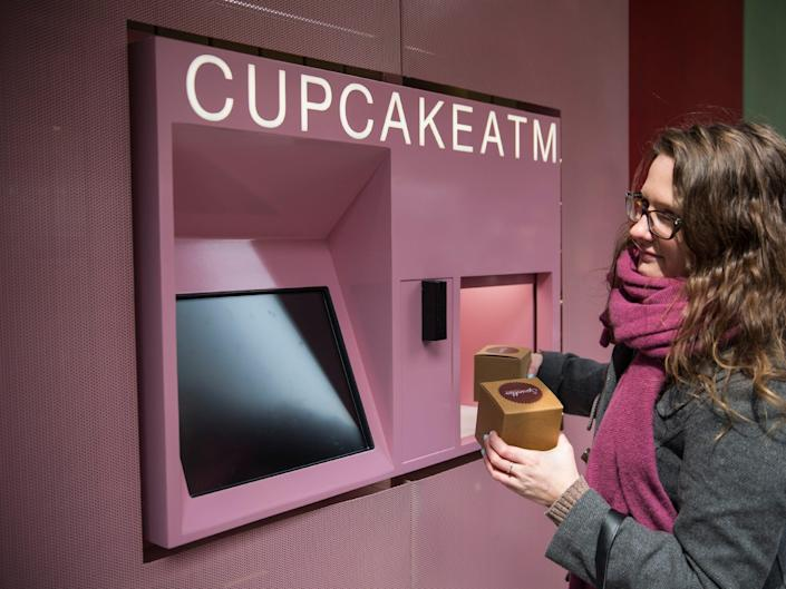A customer uses a Cupcake ATM at Sprinkles Cupcakes.