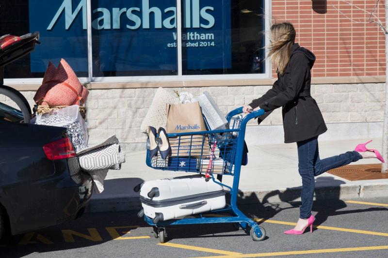 A woman with a shopping cart outside of a Marshalls store.