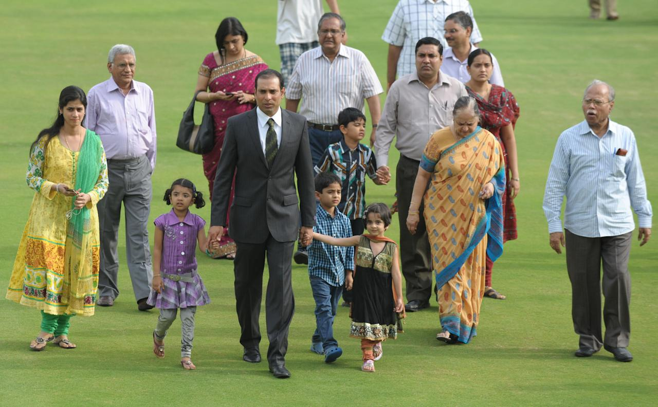 Indian cricketer Vangipurappu Venkata Sai (VVS) Laxman (4th L, in suit) arrives with family members for a press conference held to announce his retirement from Test Cricket at the Rajiv Gandhi International cricket stadium in Hyderabad on August 18, 2012. Veteran Indian batsman Vangipurappu Venkata Sai Laxman announced his retirement from international cricket on Saturday, saying it was time to make way for the next generation.   AFP PHOTO / Noah SEELAM