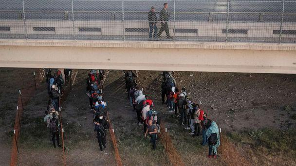 PHOTO: Law enforcement officials walk overhead as migrants await to get on a Customs and Border Protection bus out of a makeshift camp along the International Bridge in Del Rio, Texas, Sept. 24, 2021. (Adrees Latif/Reuters)