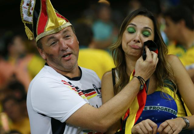 A Germany fan consoles a Brazil fan (R) during their 2014 World Cup semi-finals at the Mineirao stadium in Belo Horizonte July 8, 2014. REUTERS/Damir Sagolj (BRAZIL - Tags: SOCIETY SOCCER SPORT WORLD CUP)