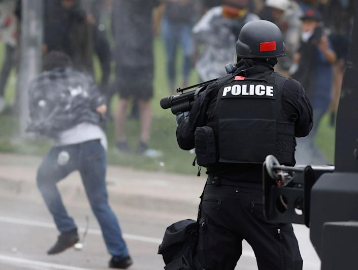 Denver Police shoot a pepper ball at a man as he retreats during a protest outside the State Capitol over the death of George Floyd, Saturday, May 30, 2020, in Denver.