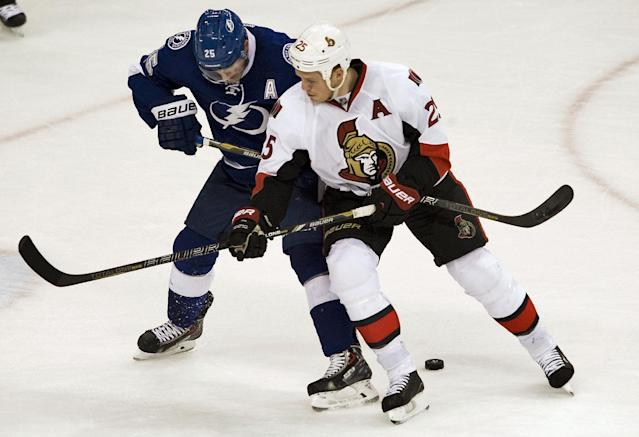 Ottawa Senators' Chris Neil, right, battles Tampa Bay Lightning's Matthew Carle, left, for the puck during the first period of an NHL hockey game on Thursday, Dec. 5, 2013, in Tampa, Fla. (AP Photo/Steve Nesius)